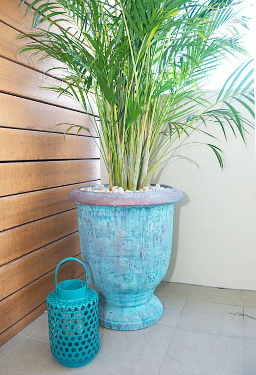 Showing a sky blue concrete urn with a golden cane and the sea in the background.